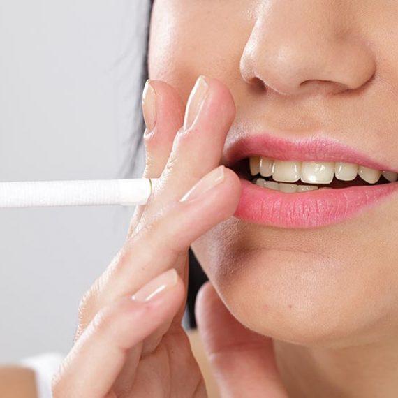 Mujer fumadora con dientes dañados por tabaco